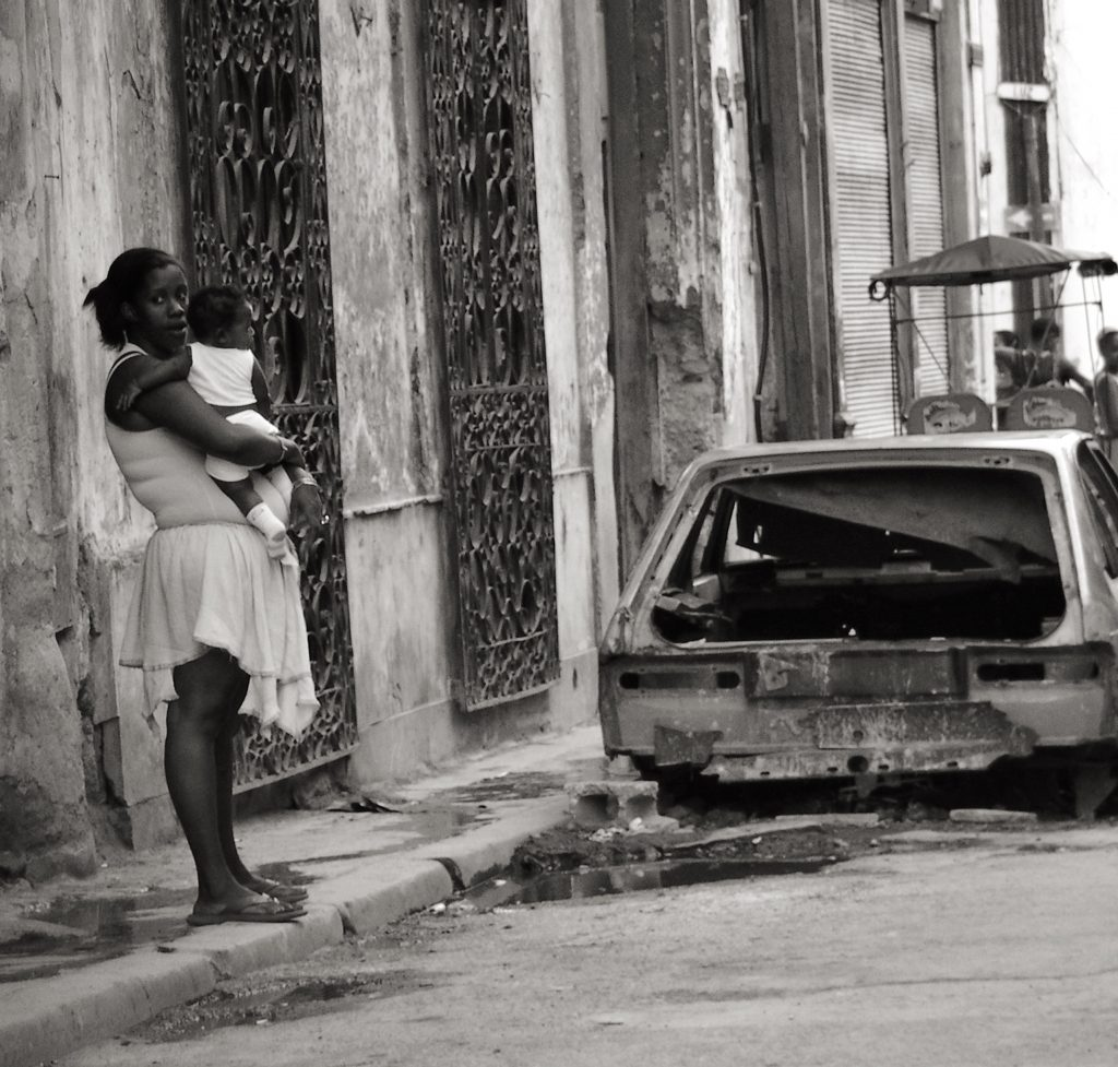 Mother holding a baby next to a disintegrating car in the crumbling street of Havana Cuba