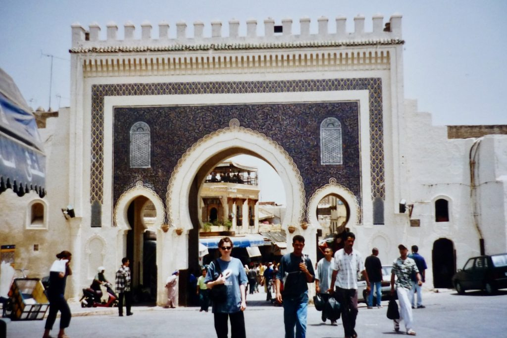 Old photo of author in front of an ornate arched gateway in Fes, Morocco