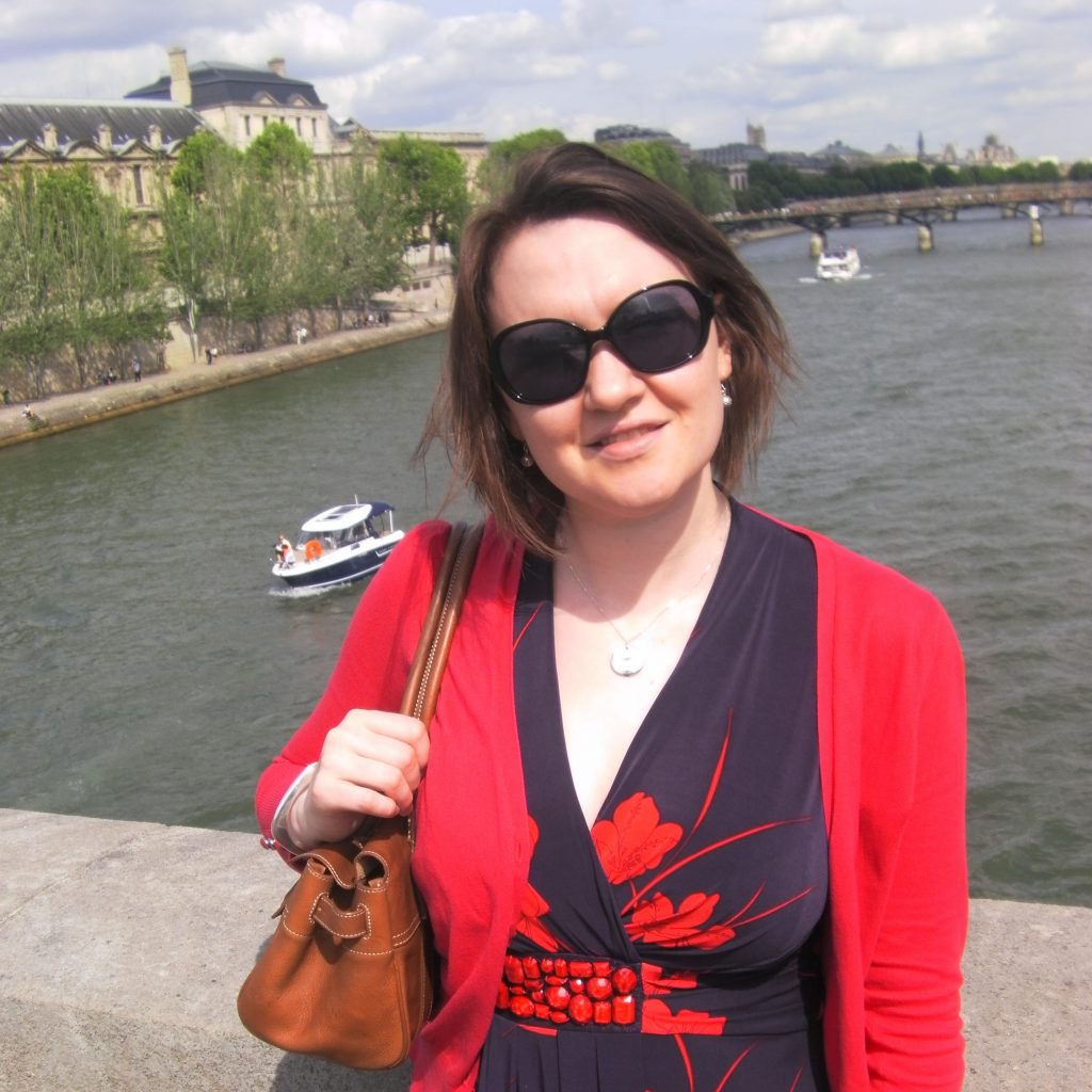 author on a bridge over the river seine in paris with the Louvre behind