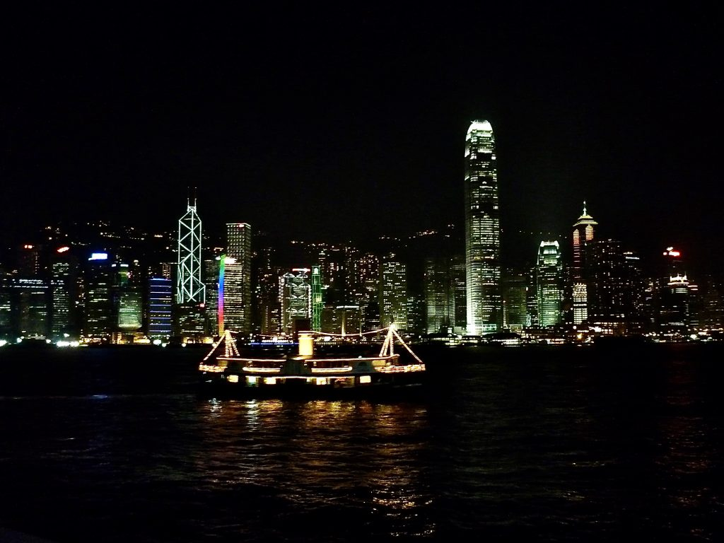 Hong Kong skyscrapers lit up at night with ferry in the foreground
