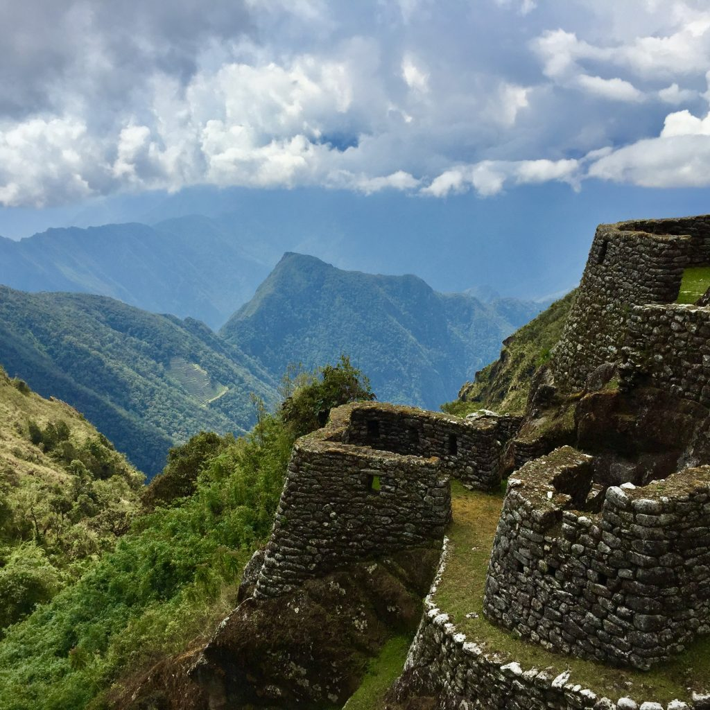View from Phuyupatamarca inca ruins towards mountains and the terraces of intipata on the inca trail in peru