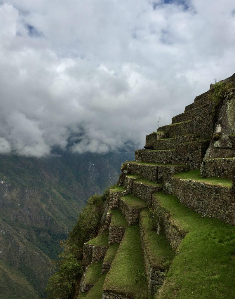 Steep green inca terraces and clouds at Machu Picchu in peru