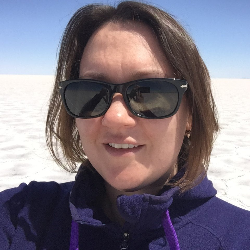Author in sunglasses on white salt flats