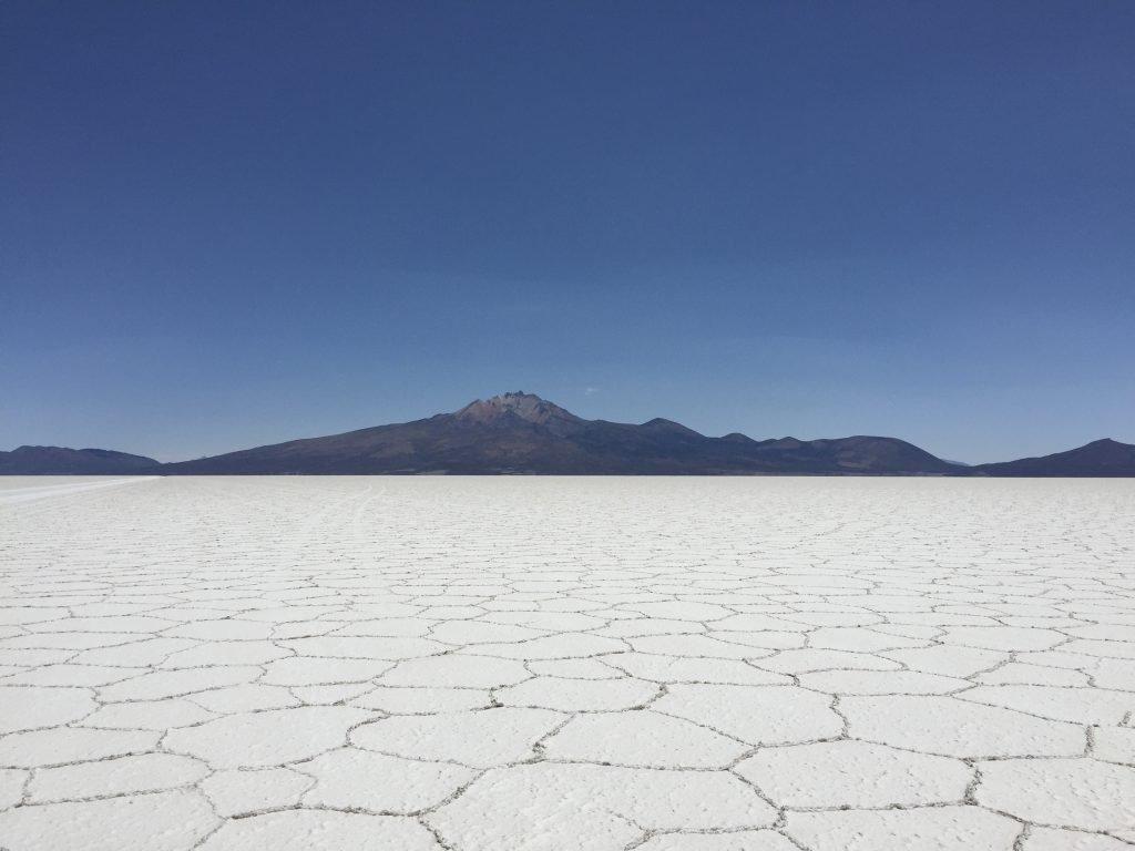 White hexagonal salt flats and black volcano at salar de uyuni in bolivia