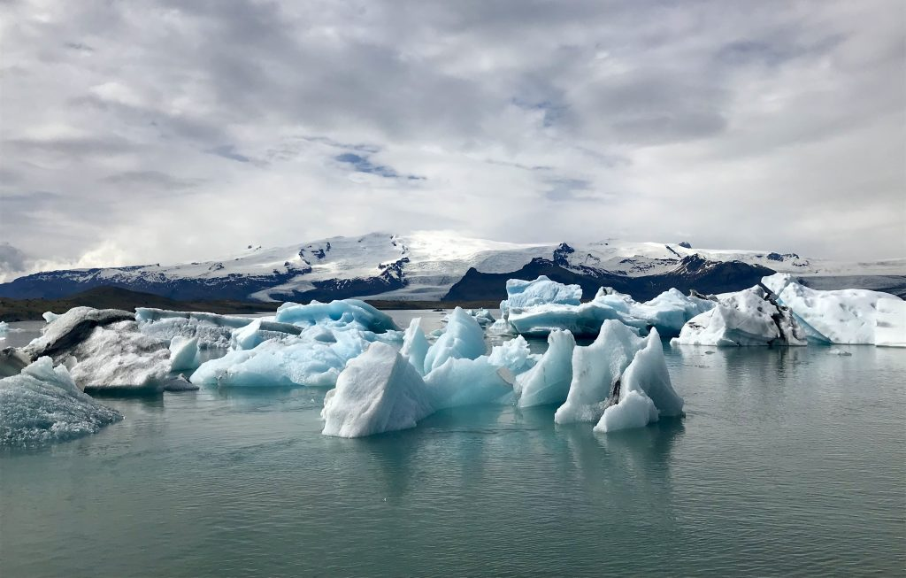 Icebergs floating in glacial lagoon with mountains and glaciers behind at Jökulsárlón in Iceland