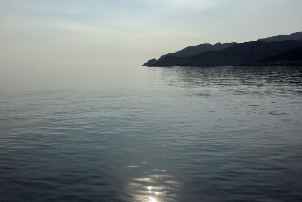 Smooth silvery water and a craggy island in the early morning light in the cyclades islands in greece