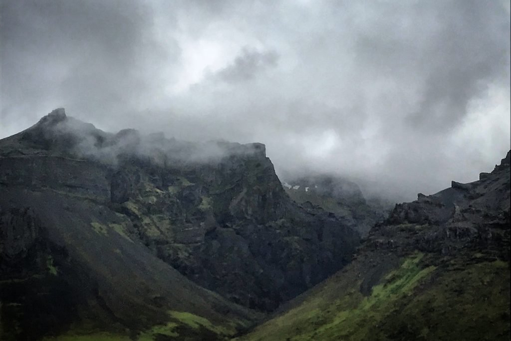 Moody craggy mountains and clouds at Hof in Iceland