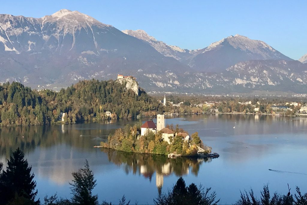 Island in the middle of lake bled, with castle and mountains behind