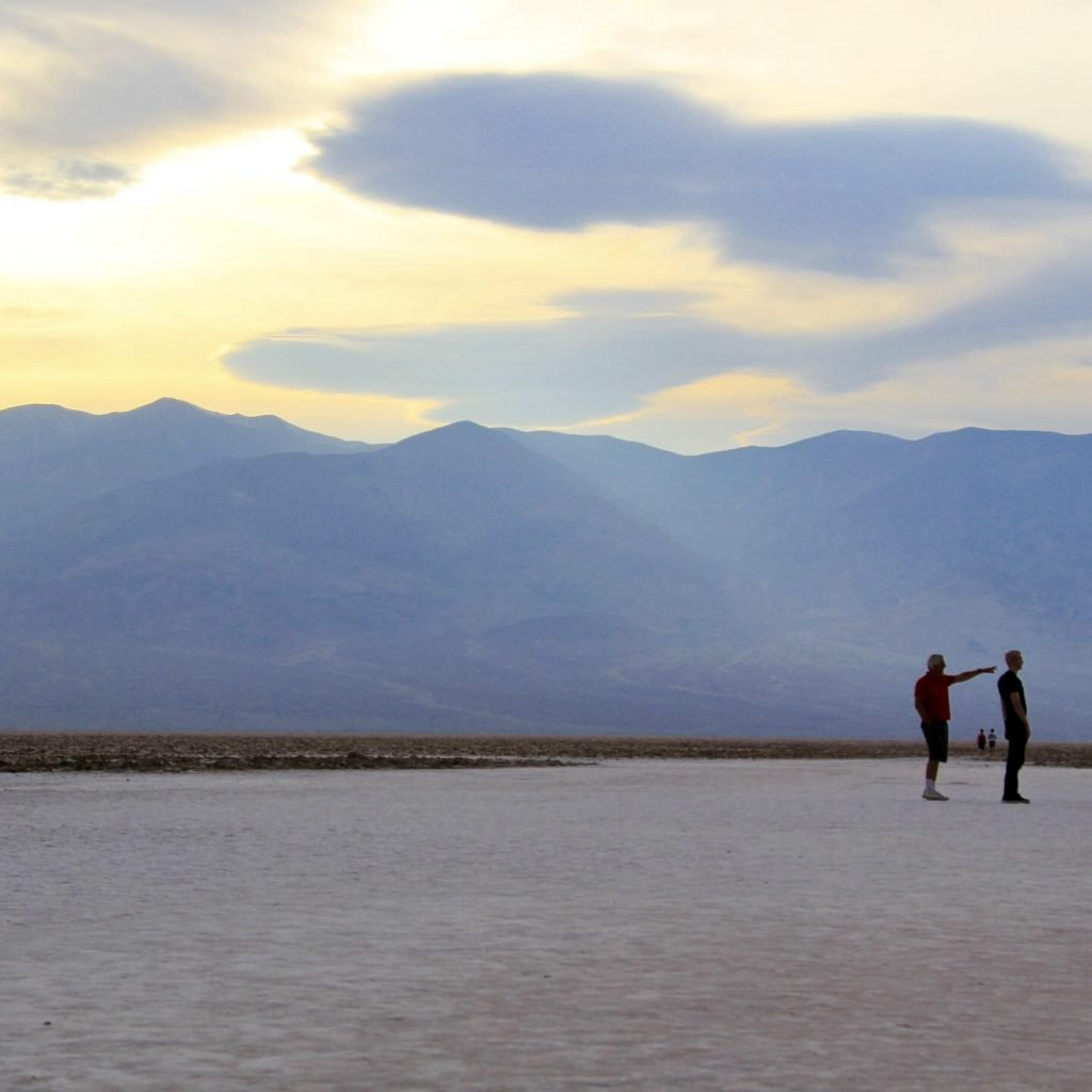 Two small figures on the badwater salt flats at dusk dwarfed by the blue mountains behind them