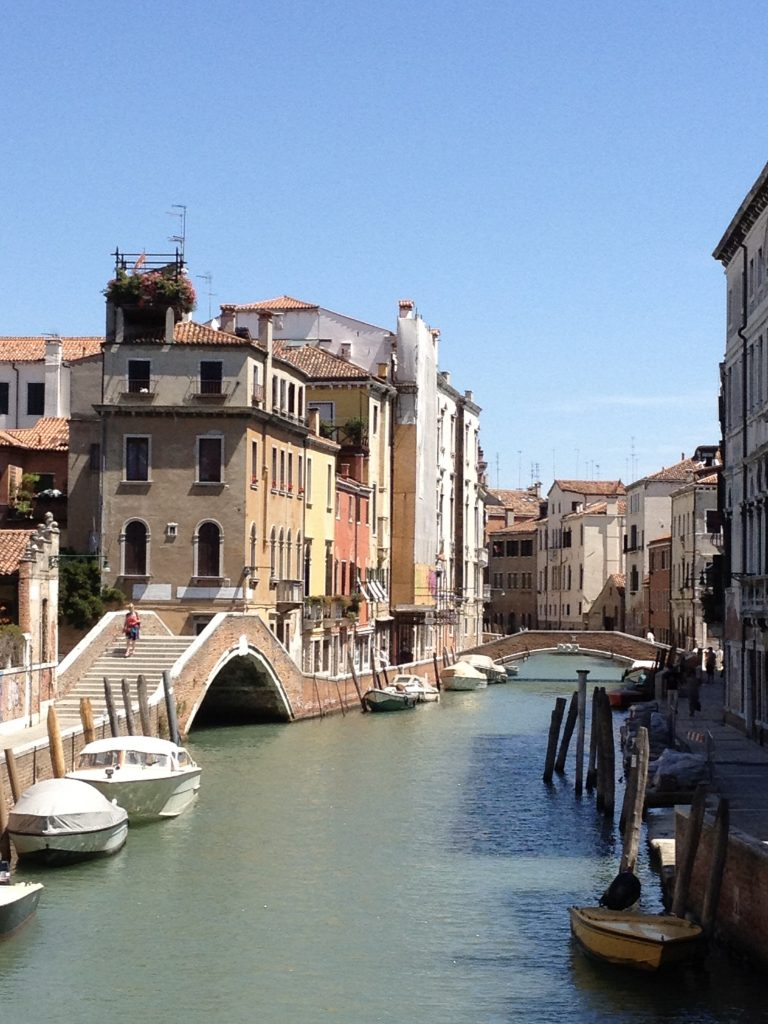 idyllic canal with a bridge and yellow and peach-coloured buildings in Venice italy