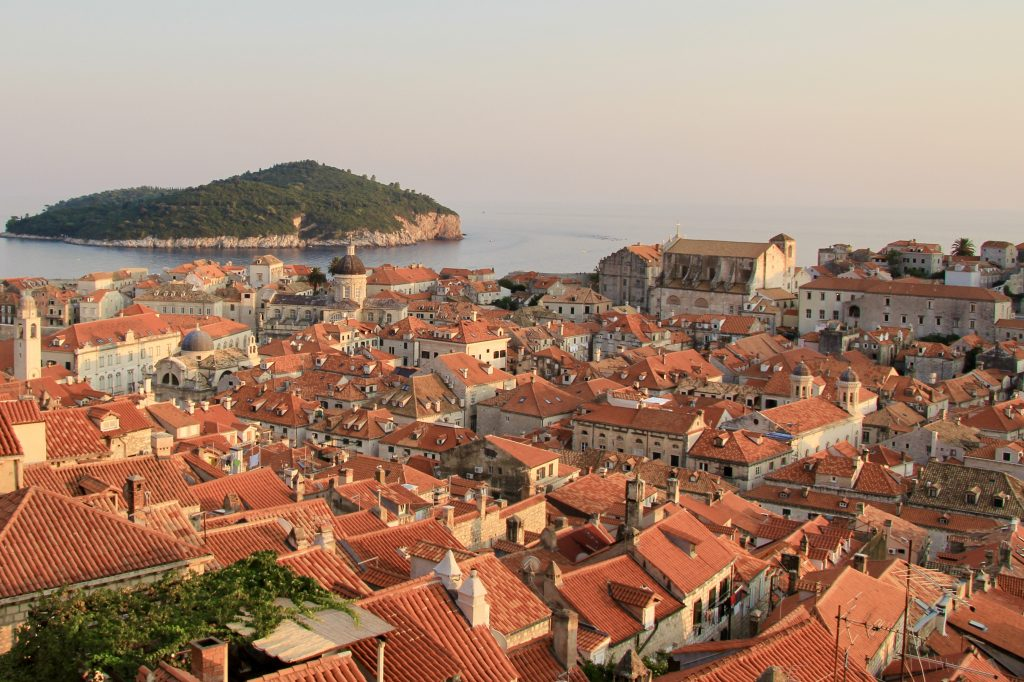 red rooftops of Dubrovnik glow in the light of the setting sun