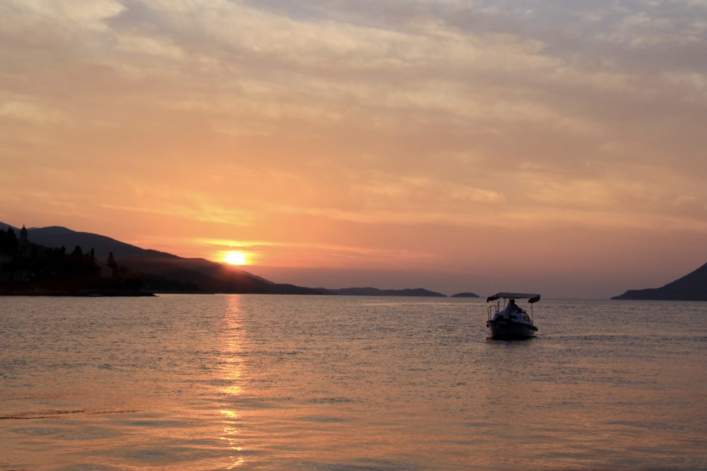 pink sunset reflected in the sea, silhouetting an island and a fishing boat in Korcula croatia