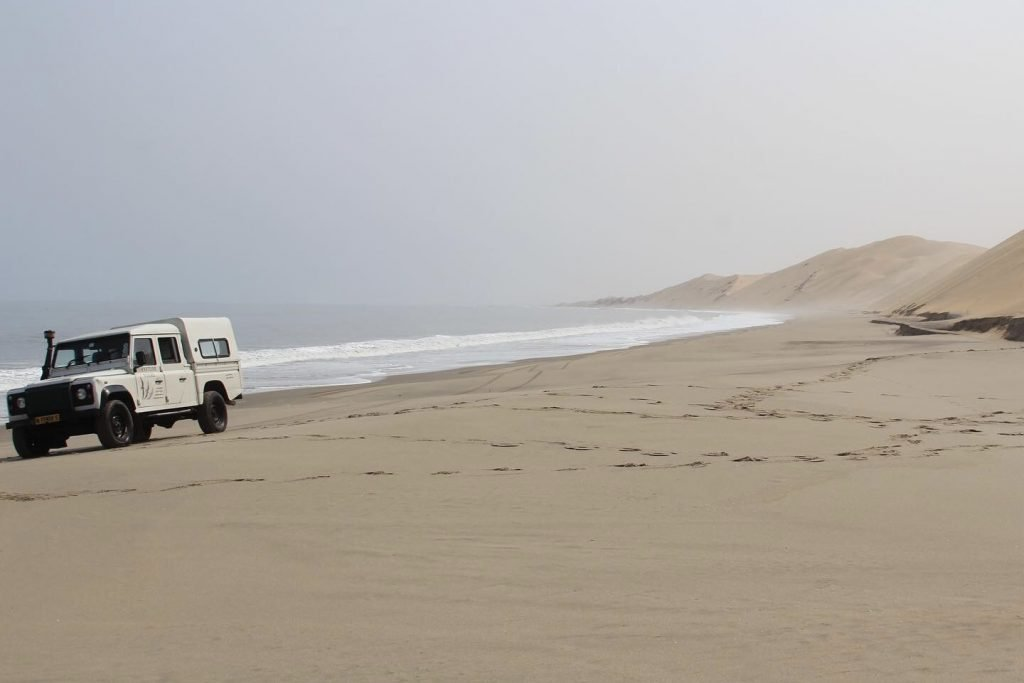 4x4 truck on the sand between the atlantic ocean and the sand dunes of the namib desert at sandwich harbour