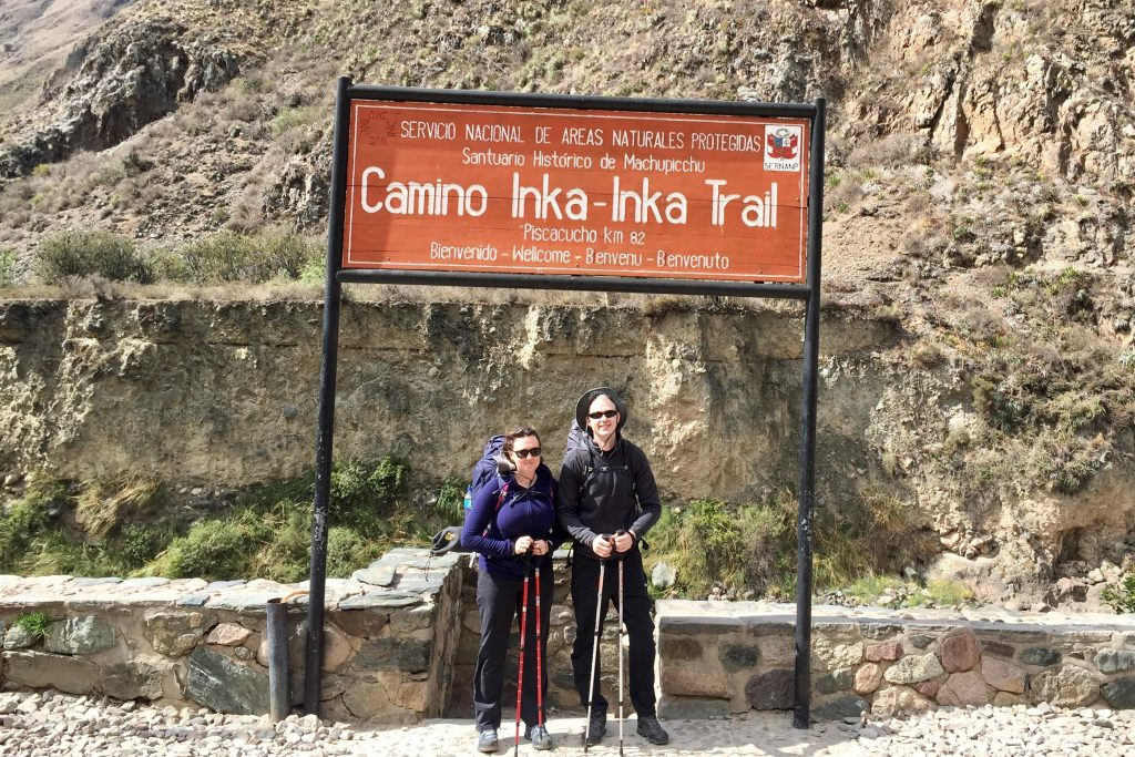 Two excited-looking hikers with backpacks and walking boots at the sign marking the start of the Inca Trail