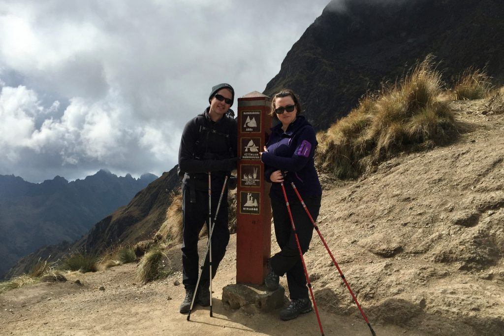 Hikers at the highest point of the inca trail dead womans pass pointing to sign which says 4200m above sea level