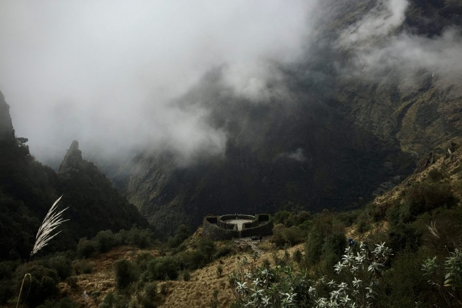 Inca outpost overlooking valley swirling with clouds on the inca trail to machu picchu