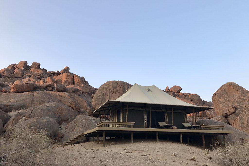 tented cabin by huge boulders at Boulders safari Camp in the namibrand nature reserve