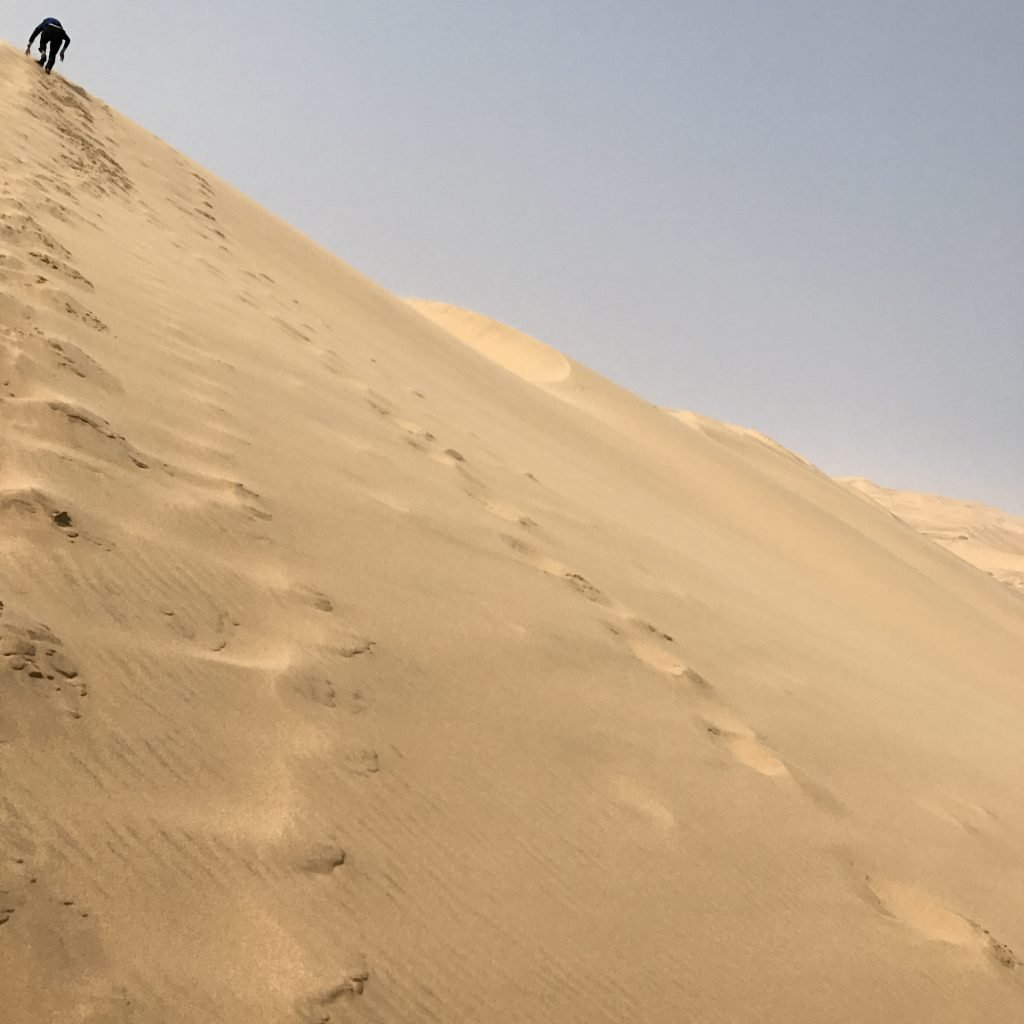 someone climbs a steep yellow sand dune at sandwich harbour in the namib desert