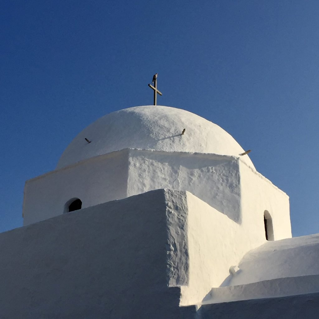 White washed Greek church with domed roof and cross in Folegandros in the Cyclades