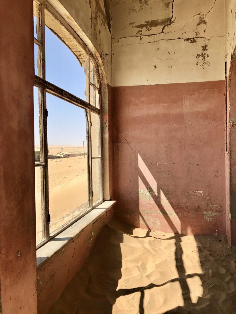 inside a deserted house with peeling paint and broken window at kolmanskop in the namib desert