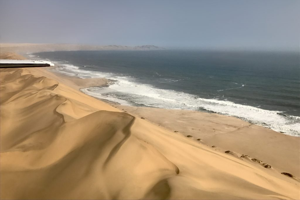 Towering golden sand dunes seen from a small plane at sandwich harbour in namibia