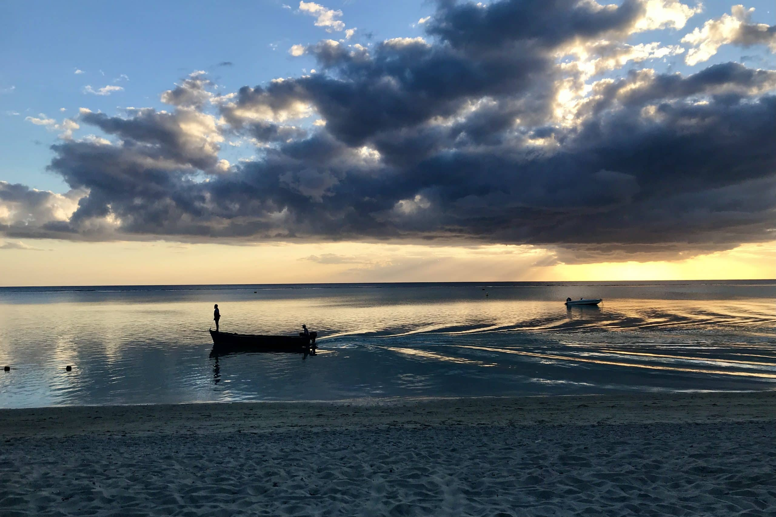Fishing boat comes home across smooth water reflecting the sunset in Mauritius