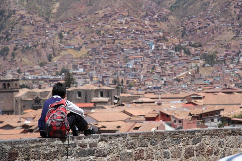 Schoolboy sits on a wall overlooking the red rooves and hillside houses of Cusco in Peru