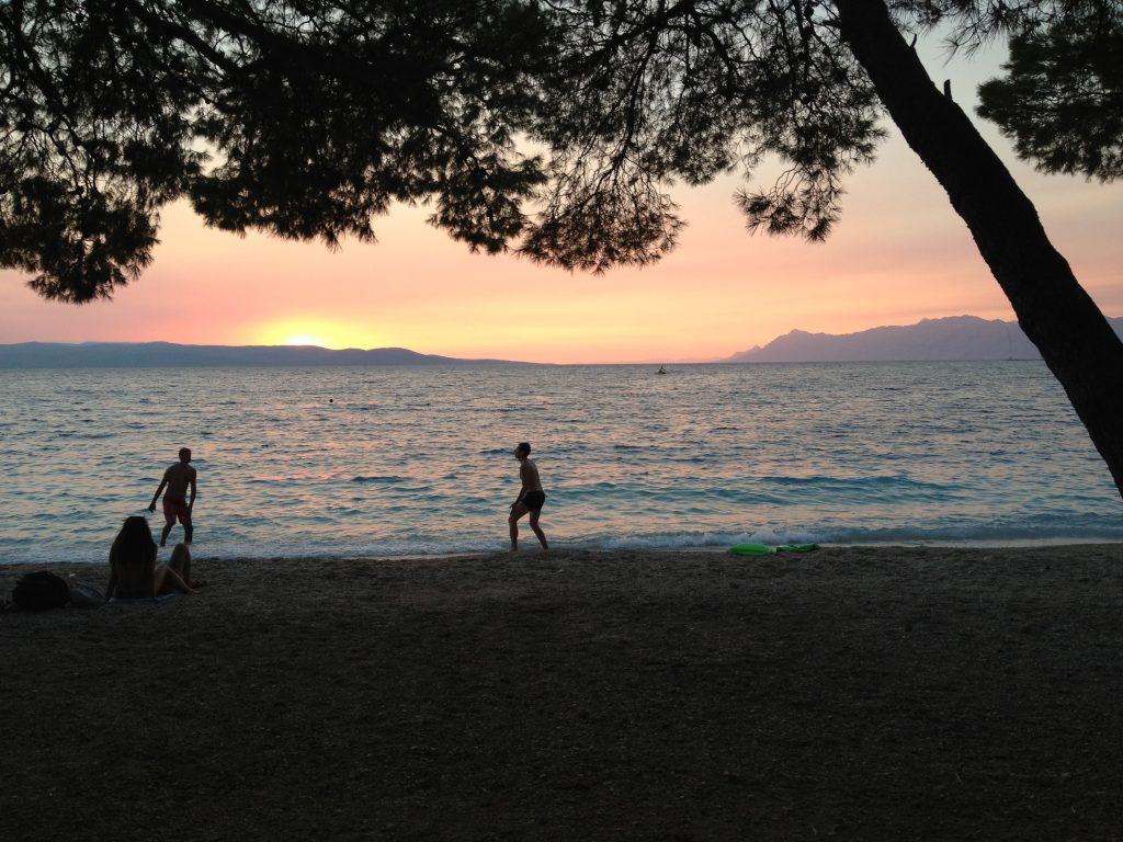 Children playing in the sunset at Makarska beach in Croatia