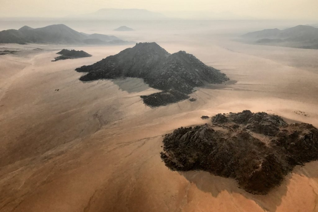 Rocky black mountains surrounded by gravel plains in namibia