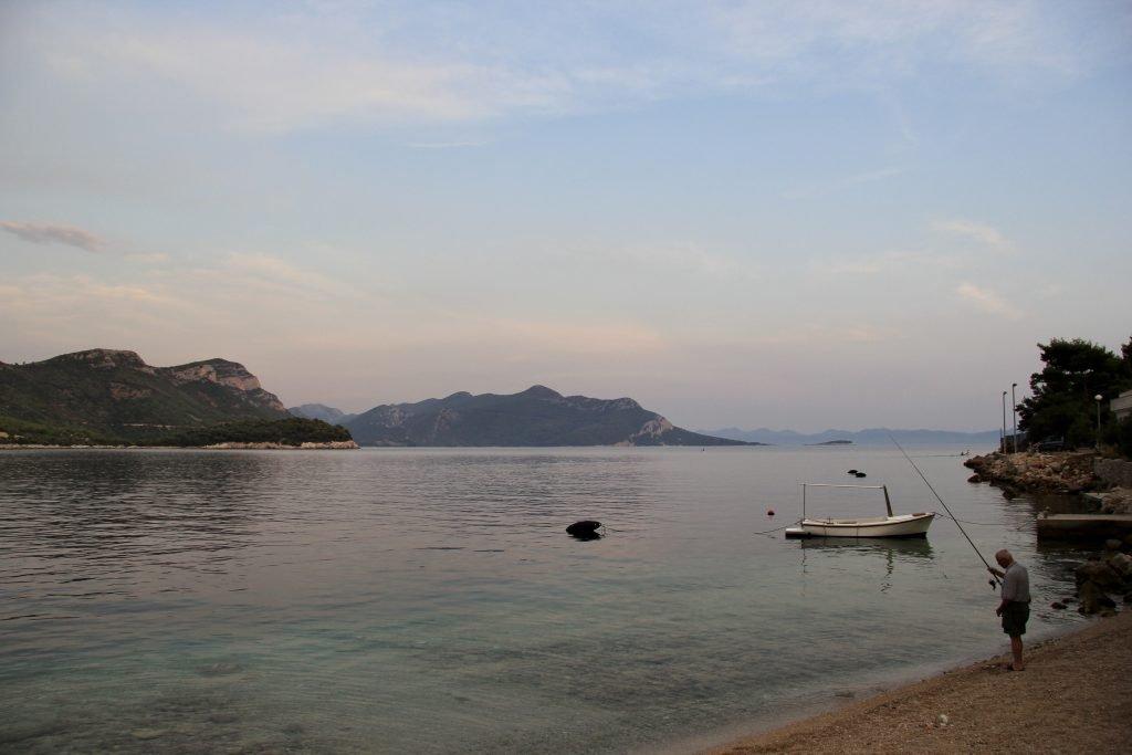 Man fishing in the calm smooth water of Trstenik in Croatia