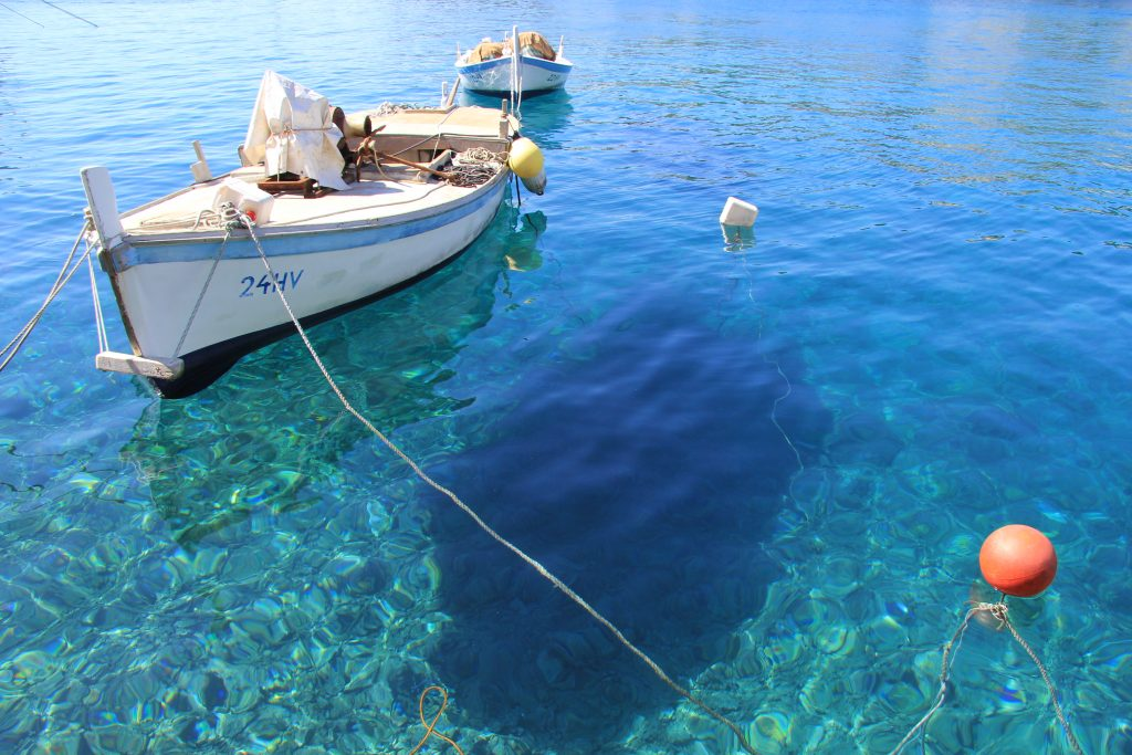 coat floating on crystal clear turquoise water in Hvar Town harbour