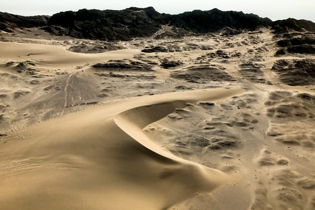 barchan dune formed on the rocky coastline of namibia