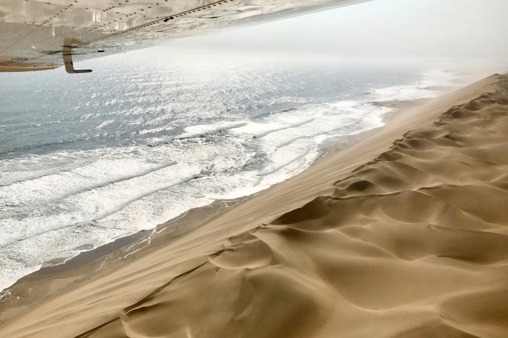 Towering sand dunes meet the atlantic ocean in namibia