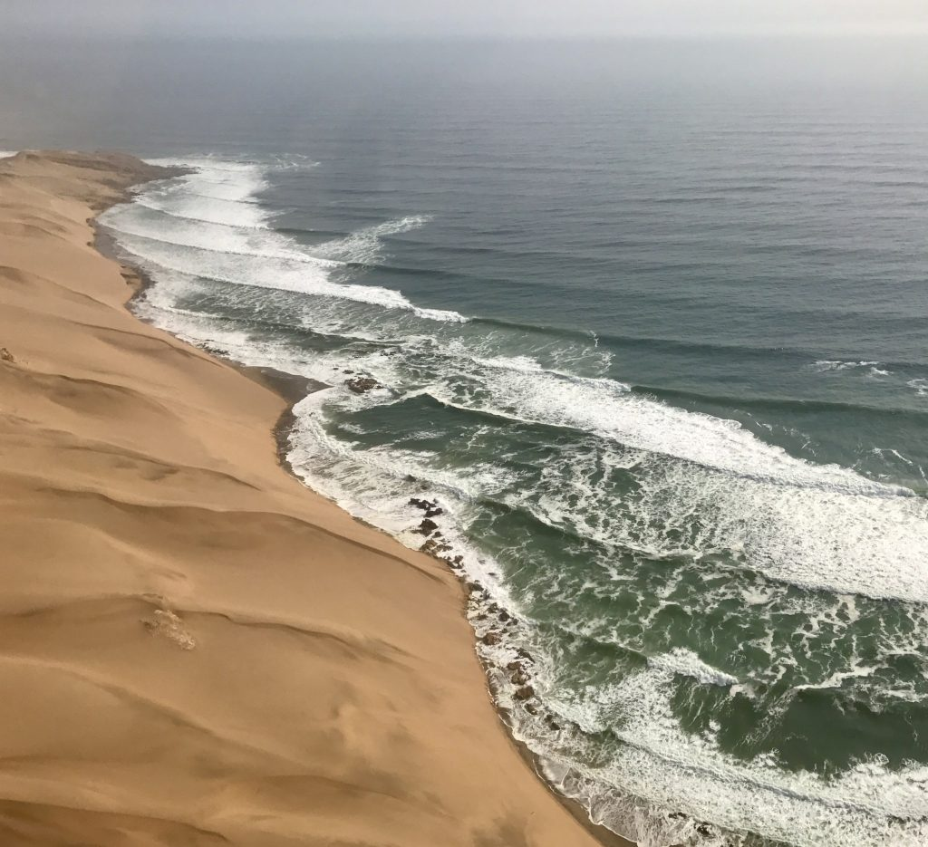 yellow sand dunes and teal coloured sea on the coastline of namibia
