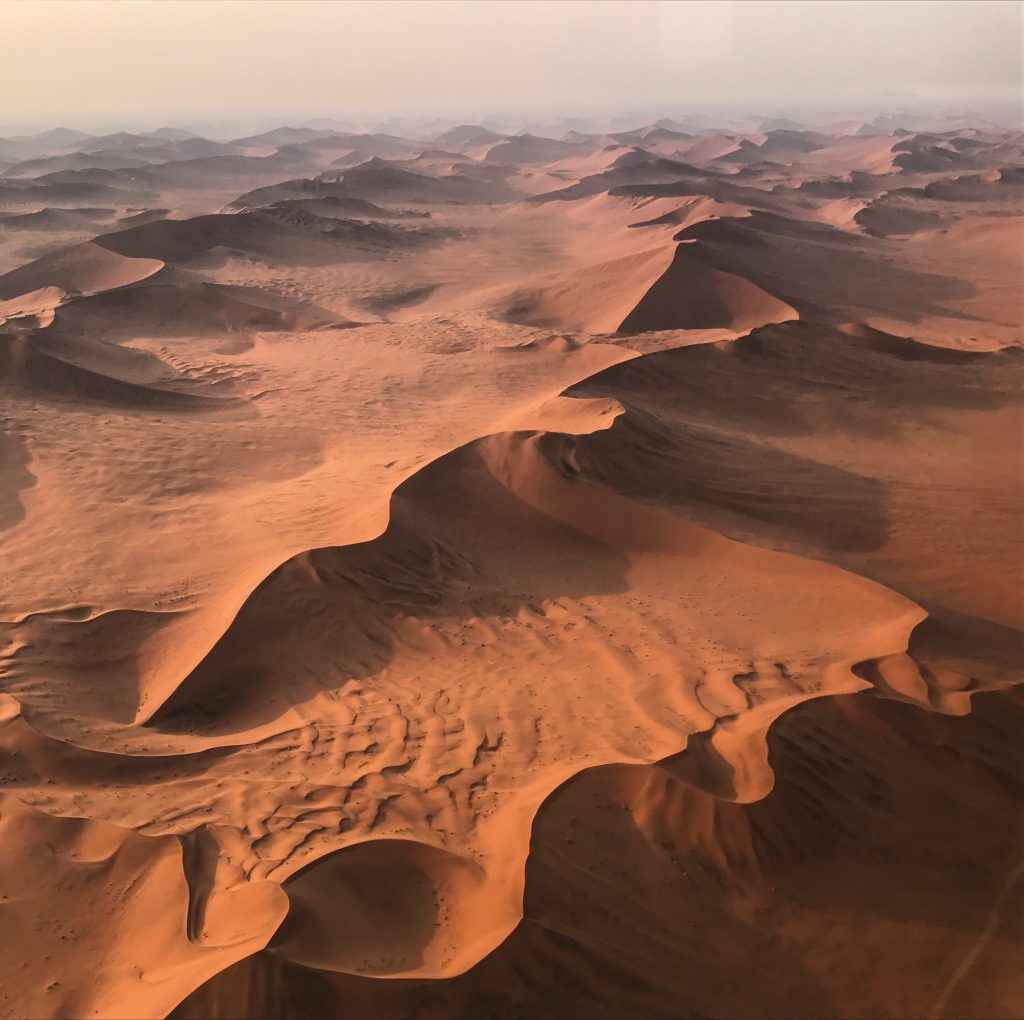 Giant snaking sand dune formations in the namib desert seen from a scenic flight over namibia