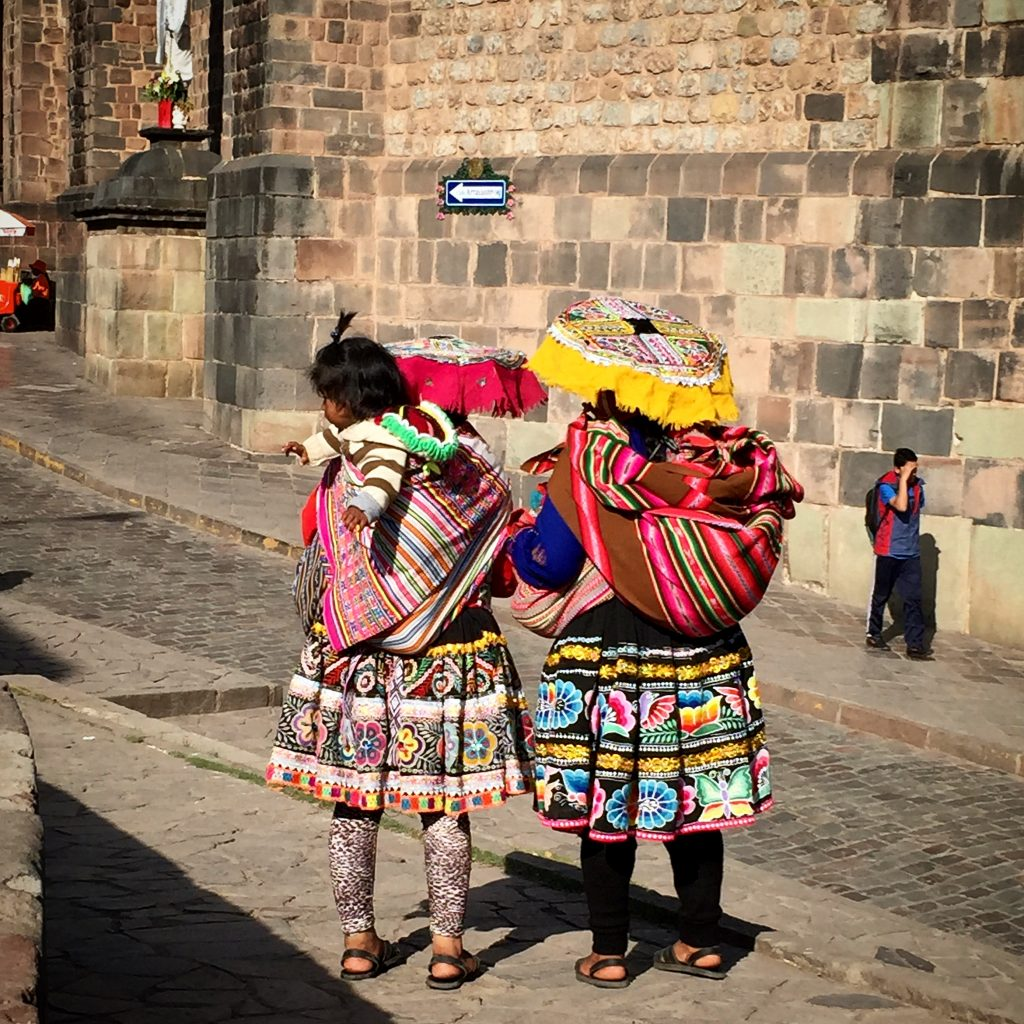 Two ladies and a baby in bright traditional dress in the streets of Cusco Peru