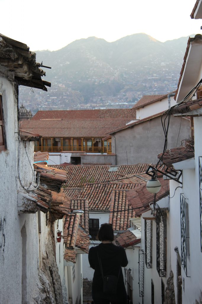 photographer overlooking the narrow streets and red rooftops of Cusco in Peru