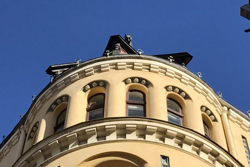 the cat hour a yellow art nouveau building in Riga with a cat on its roof