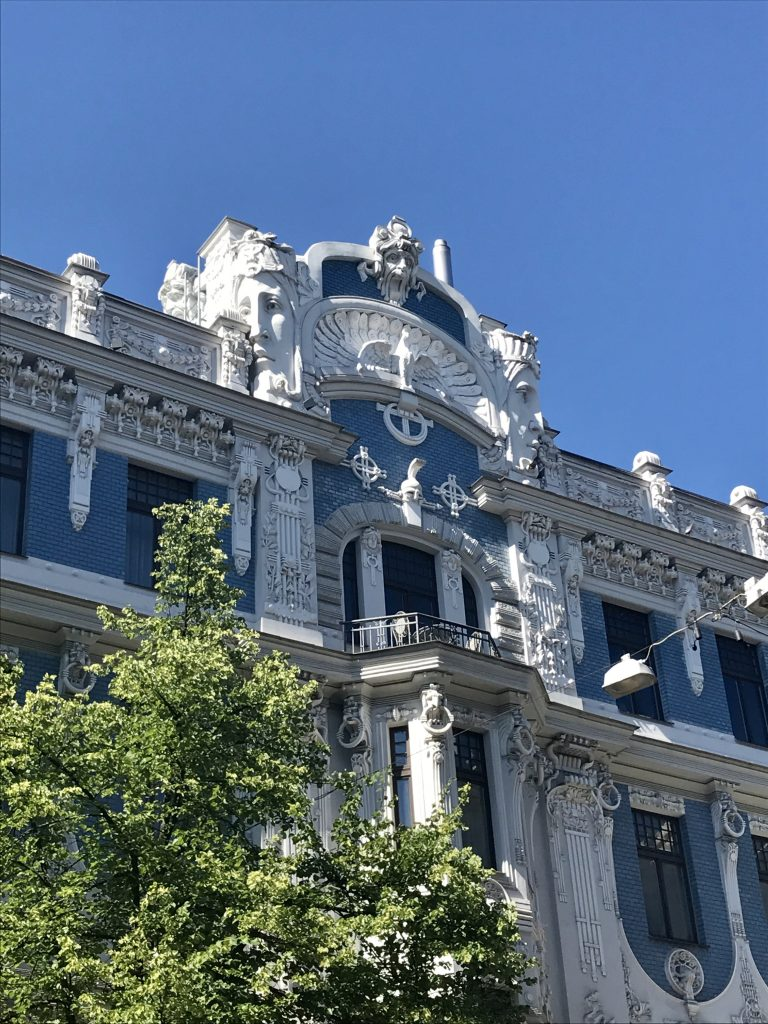 The ornate art nouveau crest with two faces on top of the mansion at 10b elizabetes iela in riga latvia