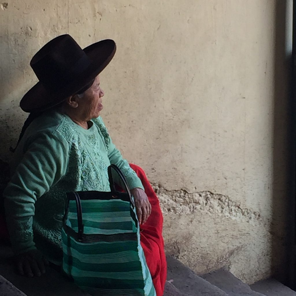 Peruvian lady in green sitting in San Pedro Market in Cusco