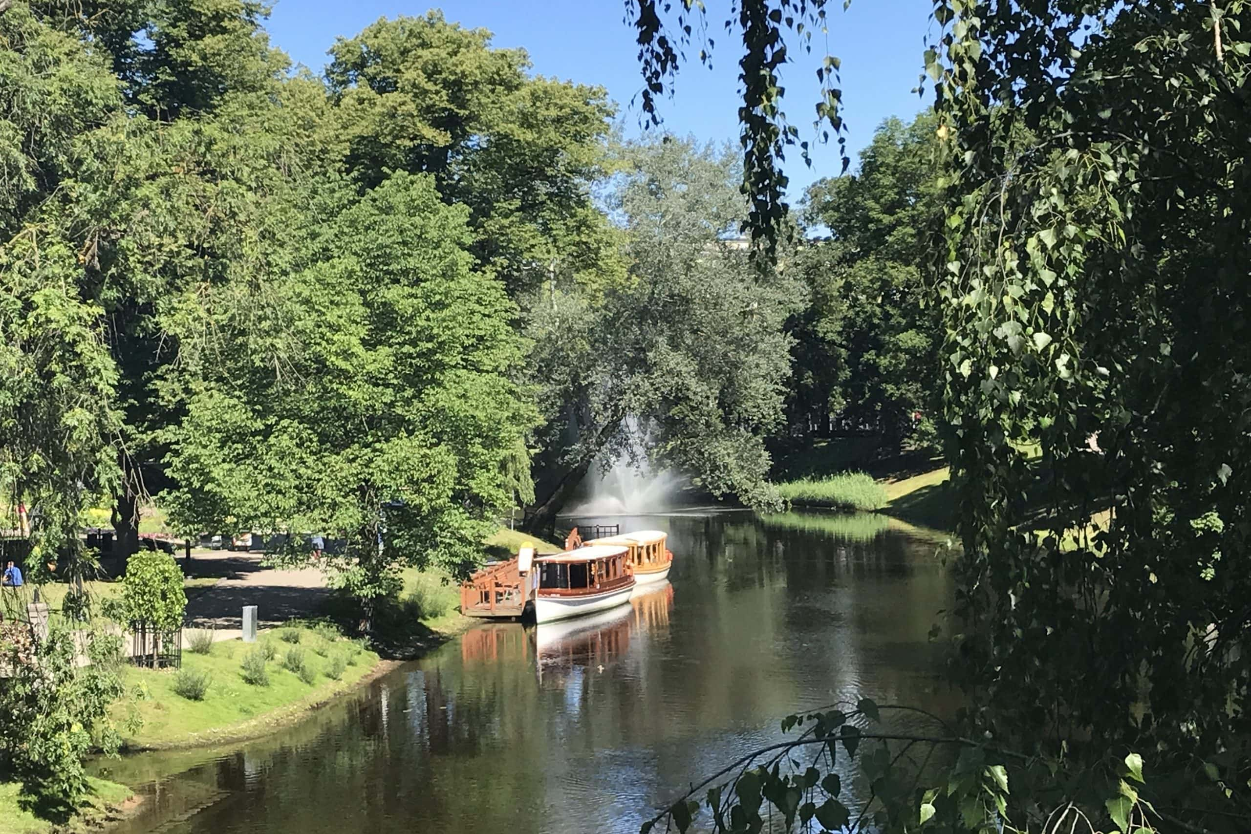 canal and wooden boat surrounded by trees in riga in latvia