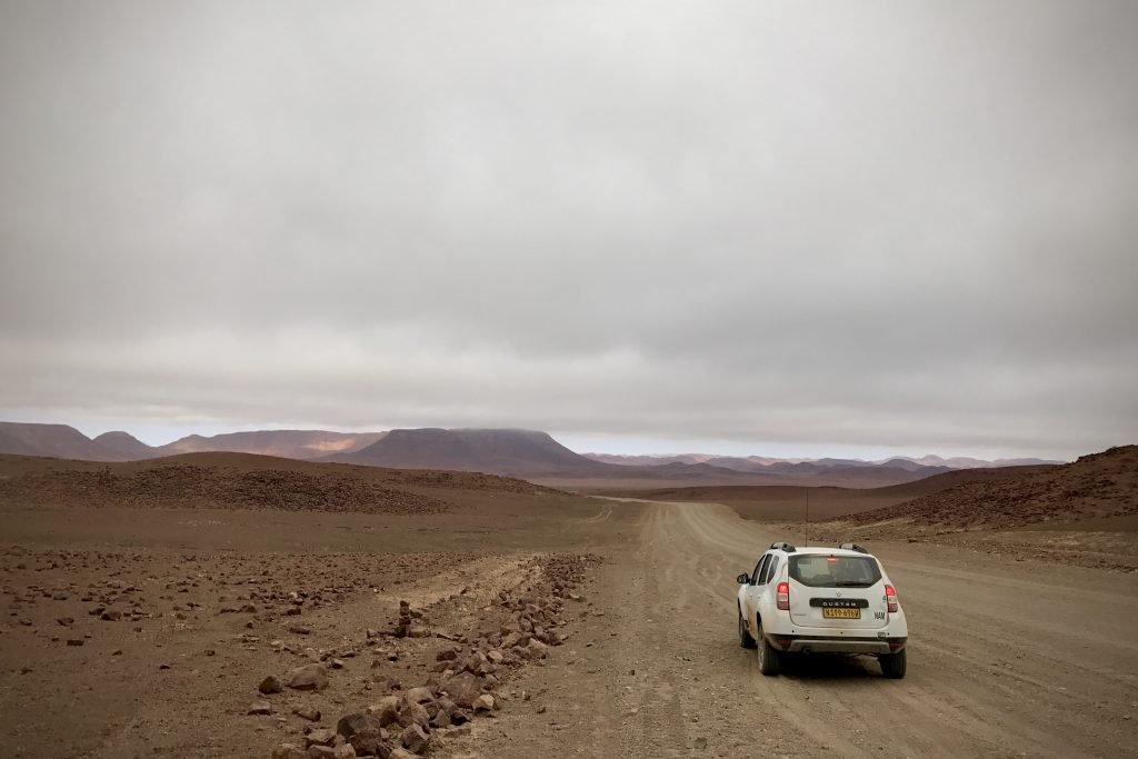 White Duster car on a gravel road between canyons in Namibia