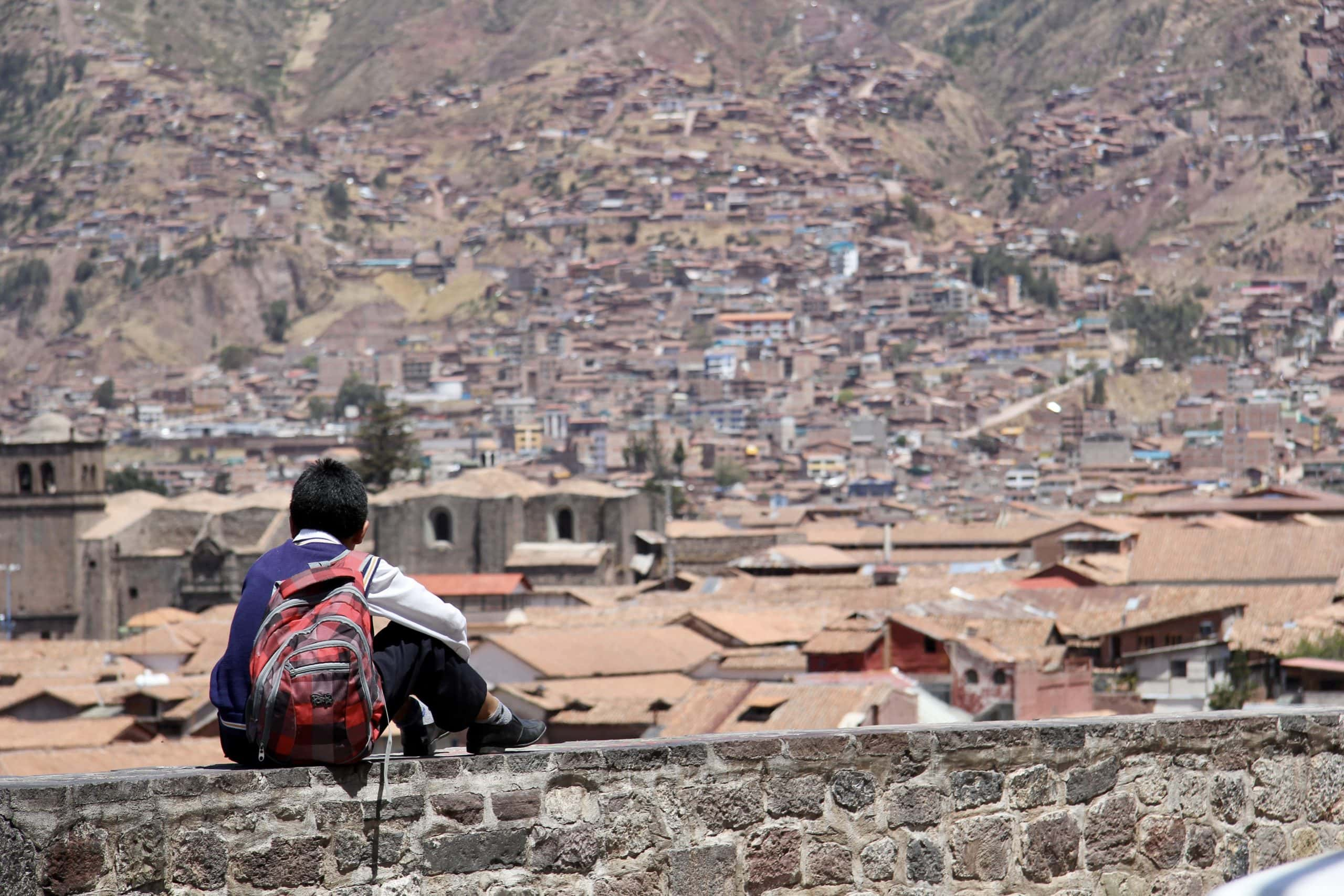 Boy sits overlooking the red rooftops and sloping hills of cusco in peru
