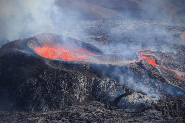 black crater and red ht lava at the erupting volcano in Iceland