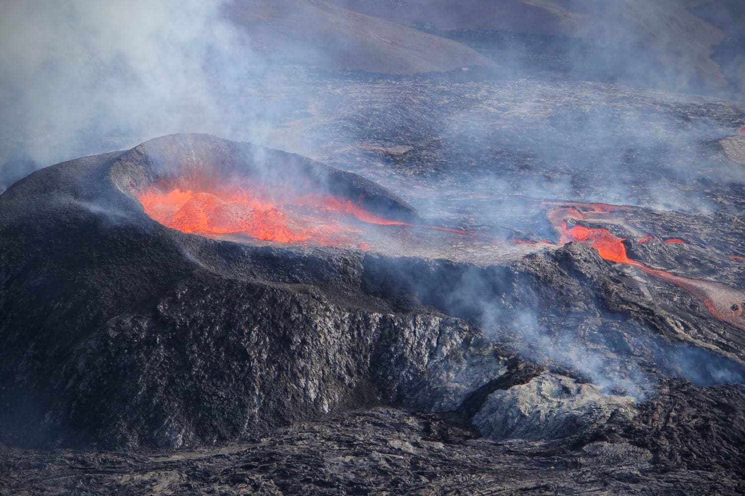 erupting volcano crater with molten red lava in Iceland