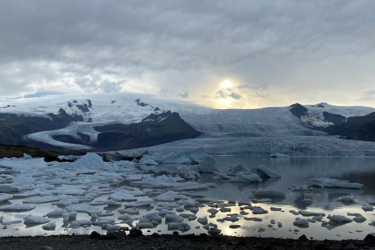 two glaciers leading to a glacial lagoon with icebergs floating in it at Fjallsárlón in Iceland