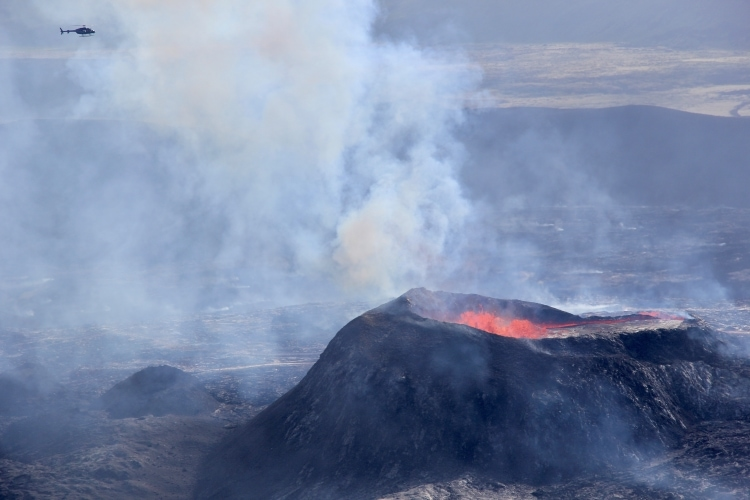 Huge erupting volcanic crater with a tiny-looking helicopter hovering over it