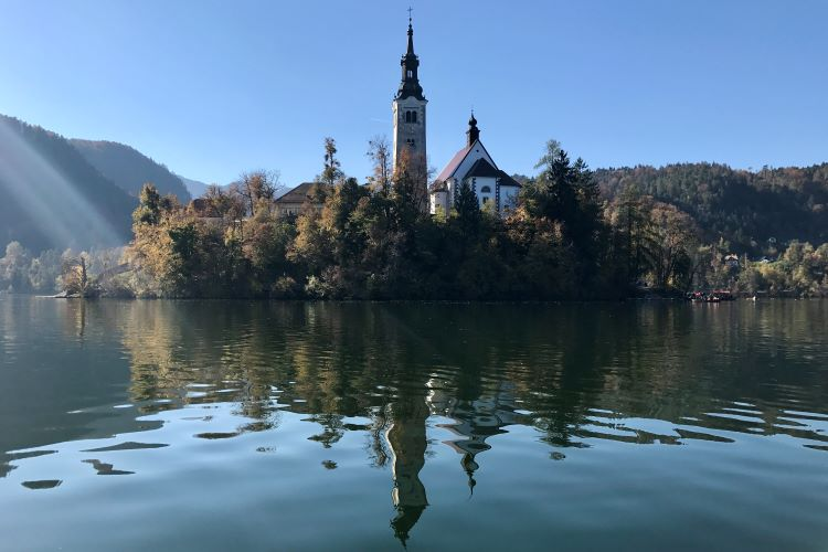 Bled island with its steeple reflected in the calm water of lake bled