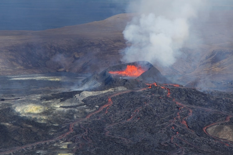 Black crater and bubbling red lava flowing in channels at the volcano in Iceland