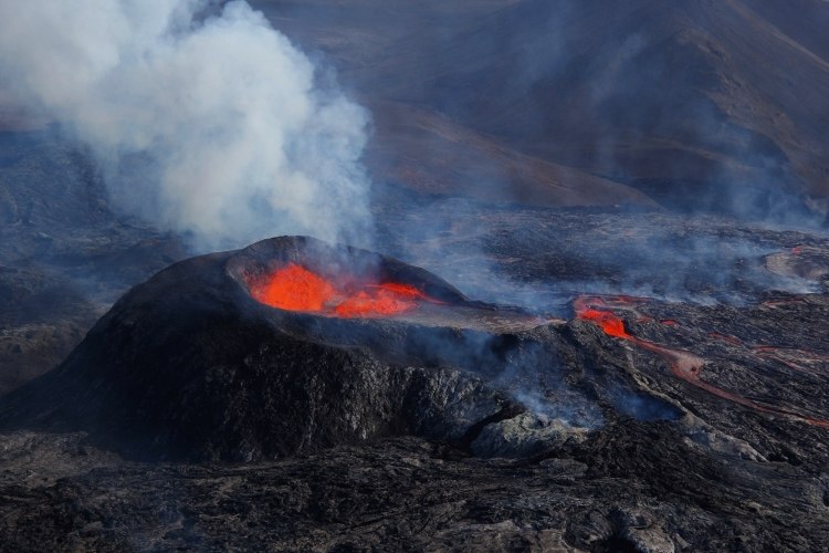 Black crater and red lava at the erupting volcano in Iceland